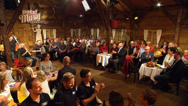 Publikum und Musikformationen in einem Holzchalet während einer Fernsehaufzeichnung.