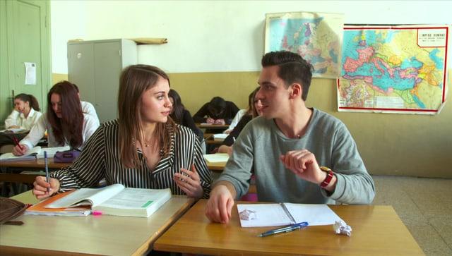 Zwei Jugendliche in der Schule sitzen an einer Schulbank.