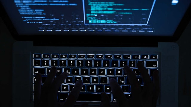 Zwei Hände auf einer beleuchteten Laptop-Tastatur.