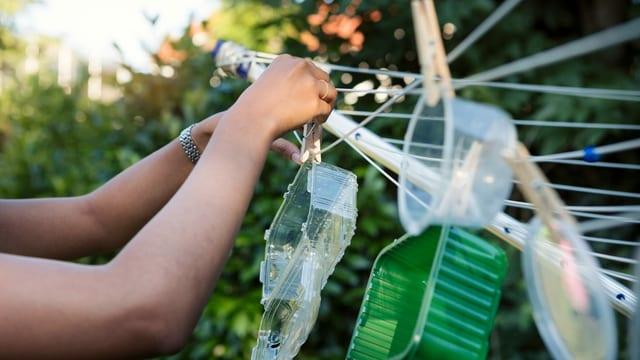 Eine junge Frau hängt Plastikschalen an eine Wäscheleine.