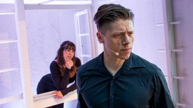 Theater: Ein Mann mit Mikrophon, hinter ihm lehnt eine Frau im Fenster.
