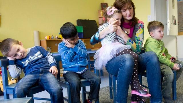 Kinder spielen mit der Spielgruppenleiterin.