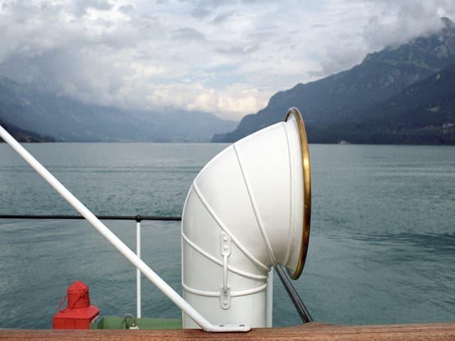 Ein weisses Schiffsrohr vor dem Hintergrund eines behangenen Himmels über einem See.