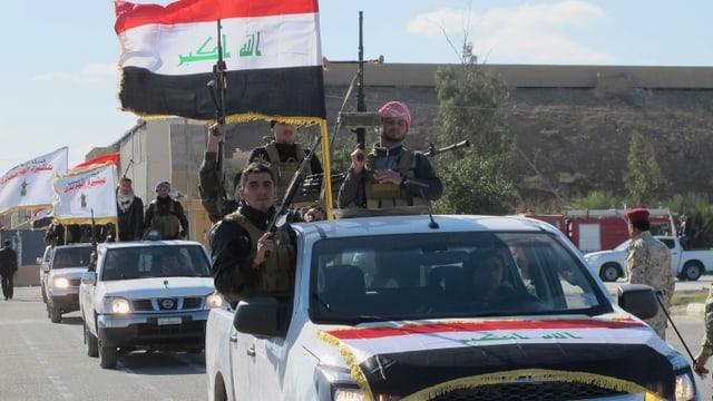 Cumbattants sunnits en autos e cun bandiera iracaisa