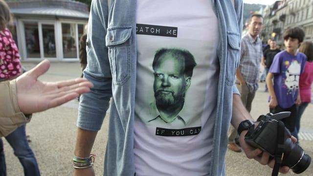 """Mann zeigt ein T-Shirt mit Fahndungs-Foto von Herrn Kneubühl und dem Satz """"Catch me if you can"""""""