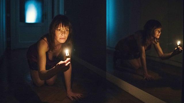 Eine Frau im Nachthemd kriecht mit einer Kerze in der Hand durch einen Flur.