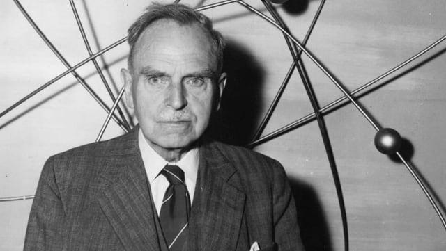 ein schwarz-weiss Foto eines Mannes vor einem Atommodell