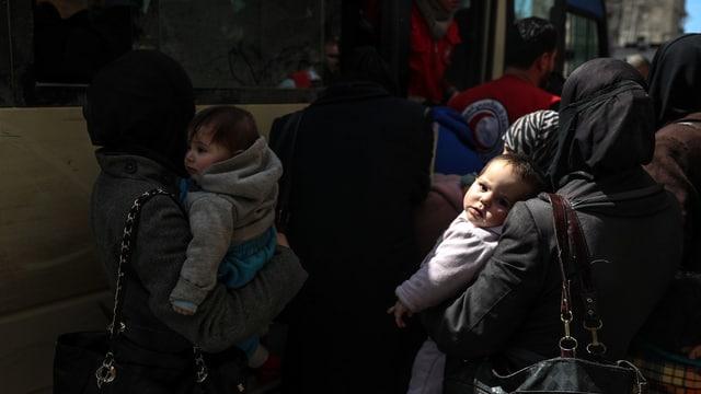 Frauen mit Kindern steigen in ein Bus ein.