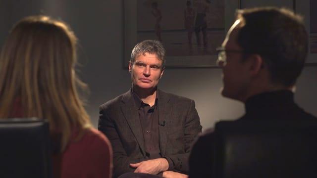 Ein Mann mit grauem Haar im dunkeln Jackett.
