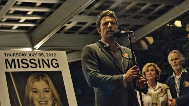 Auf dem Bild ist Ben Affleck als Nick Dunne vor einem Plakat mit seiner vermissten Frau zu sehen.
