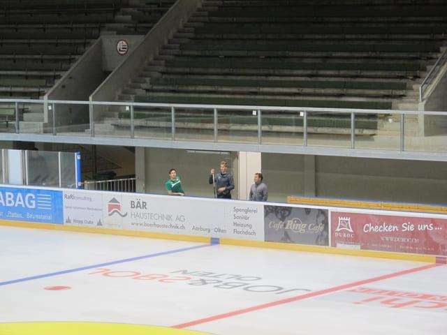 Zwei Spieler und Trainer des EHC Olten betrachten das neue Stadion