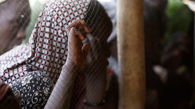 Eine Frau mit Kopftuch hinter einem Gitter, an dem sie sich mit der rechten Hand festhällt.