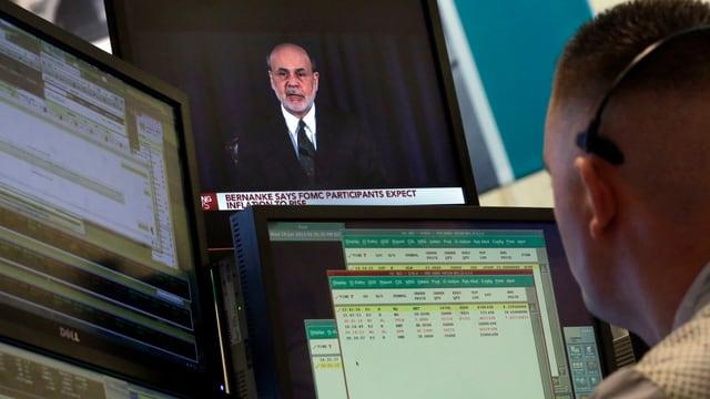 Ein Börsenhändler verfolgt eine Pressekonferenz des US-Notenbankchefs Bernanke auf einem Bildschirm.