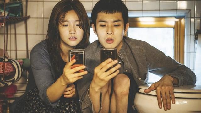 Eine junge Frau und ein junger Mann blicken staunend auf ihre Smartphones.