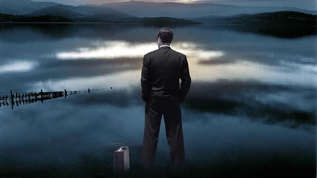 Manager mit Koffer schaut in Abendstimmung auf einen See mit Bergen im Hintergrund