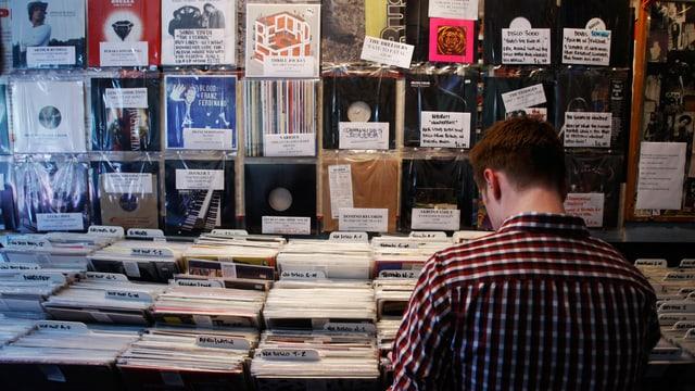 Ein Mann steht in einem Musikgeschäft vor einem Regal mit Schallplatten.