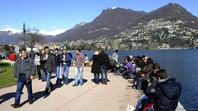 Eine Menschenmenge an der Schweizer Riviera, im Hintergrund der Luganersee, die Sonne scheint.