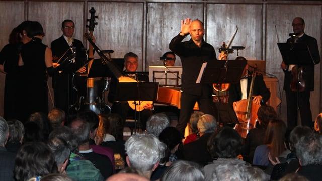 Stefano Montanari posiert auf der Bühne umgeben von Musikern.