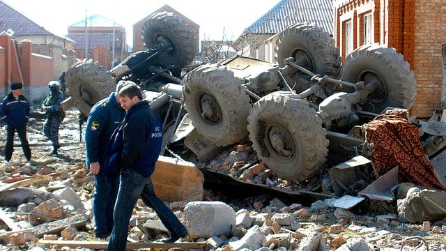 Russische Sicherheitskräfte stehen vor einem Lastwagenwrack