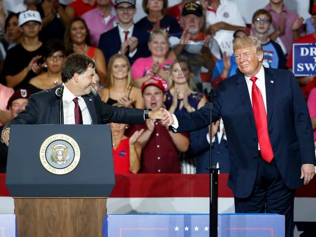 Balderson reicht Trump auf Podium die Hand.