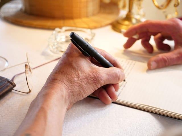 Eine Hand schreibt mit einem Füller in ein Heft.