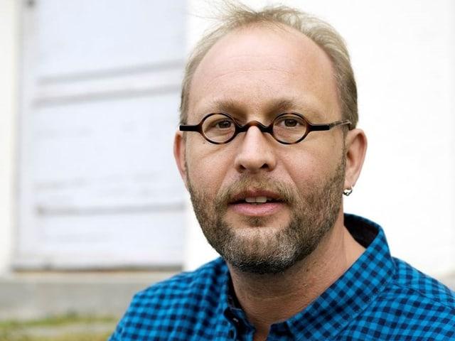 Ein Mann mit blondem Haar und Brille.