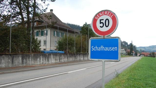 Die Ortstafel von Schafhausen, im Hintergrund das alte Schulhaus