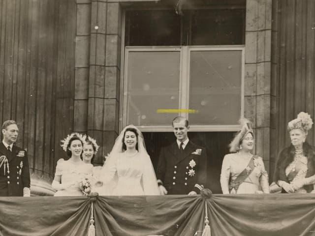 Menschen stehen auf einem Balkon. In der Mitte das Ehepaar, sie im Hochzeitskleid, er im Anzug.