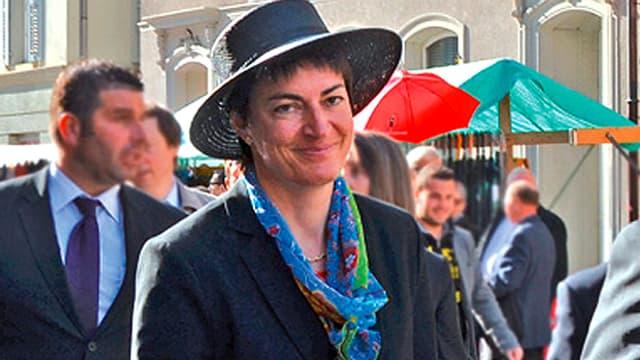 Frau mit Hut geht durch eine Strasse