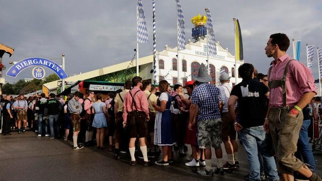 Menschen in bayrischen Kleidern warten in einer Schlange.