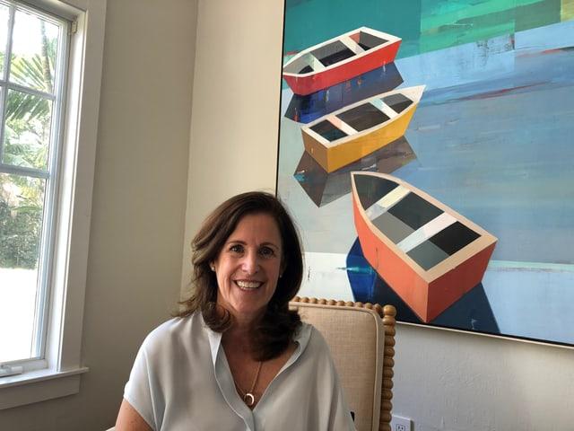 Frau vor Gemälde mit drei Booten.
