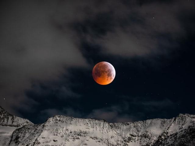 Der Mond über verschneiten Bergen.