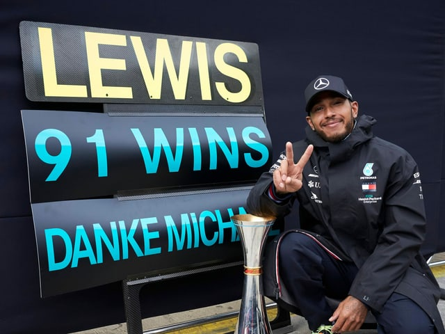 Lewis Hamilton posiert mit dem Siegerpokal