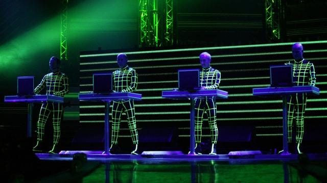 Vier Männer auf der Bühne, in schwarzen Overalls, die mit grün-blauem Licht bestrahlt werden.