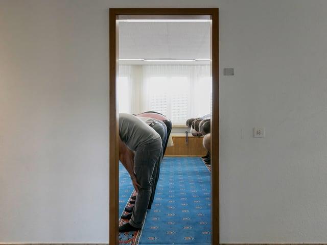 Durch eine offene Tür sieht man in den Gebetsraum. Drinnen stehen mehrere Männer, die ihren Oberkörer beugen.