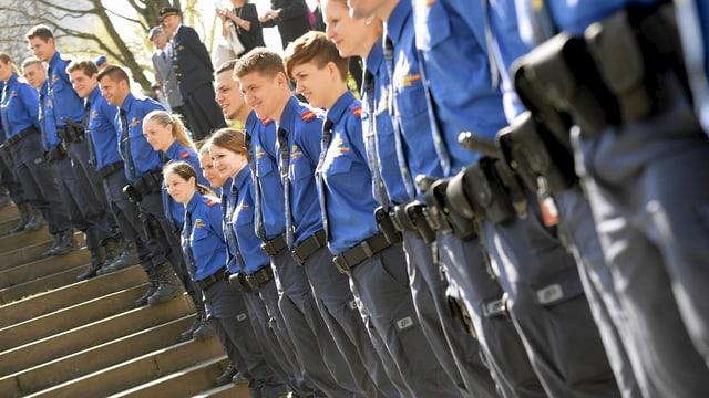 Polizisten in Uniform stehen in Reih und Gleid einer Treppe entlang