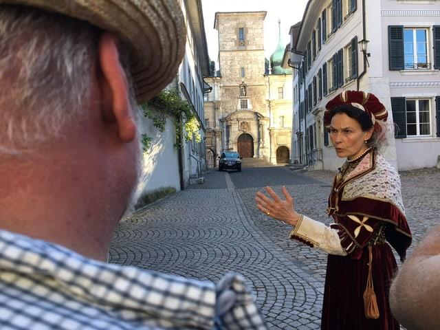 Marie-Christine Egger führt durch Solothurn, im Hintergrund das Ratshaus in dem heutzutage das Kantonsparlament tagt.