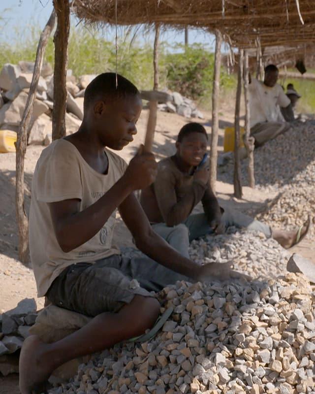 Ein Mann zerkleinert Steine mit einem Hammer.