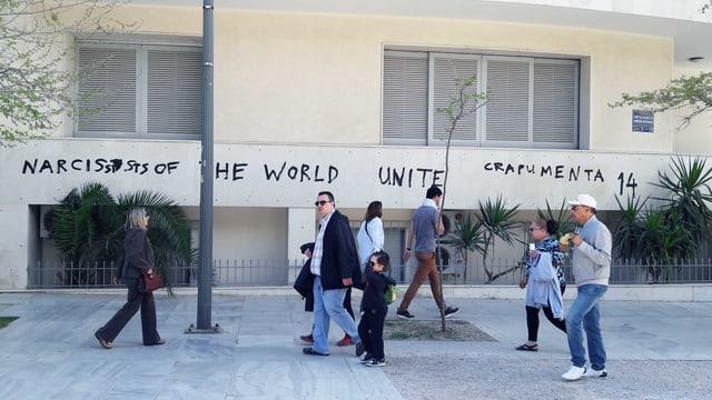 Leute laufen vor einem Gebäude auf dem steht: «Narzissten auf der Welt vereint euch. Crapumenta 14».