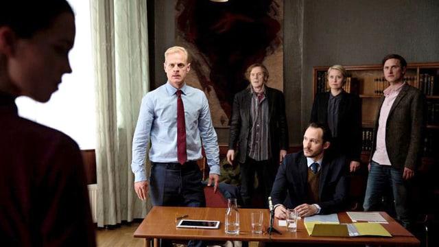Vier Menschen stehen hinter einem Tisch, an dem ein Notar sitzt.