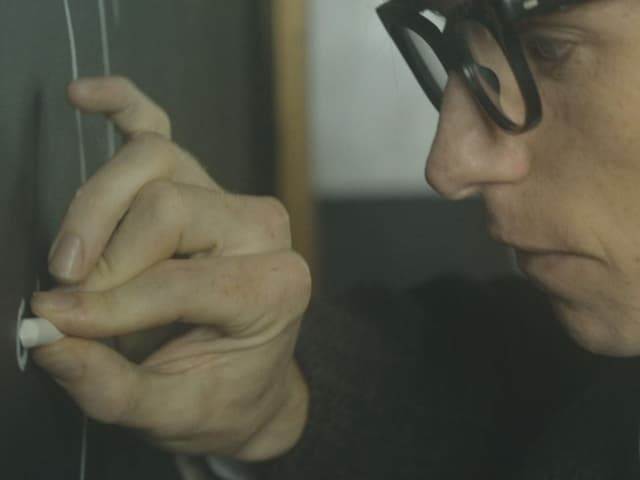 Stephen Hawking an Wandtafel schreiben