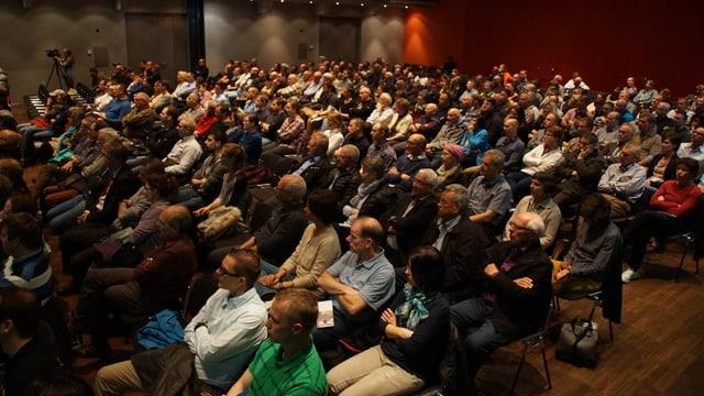 Ein Saal voller Leute. Sie sitzen zum Teil mit verschränkten Armen auf den Stühlen.