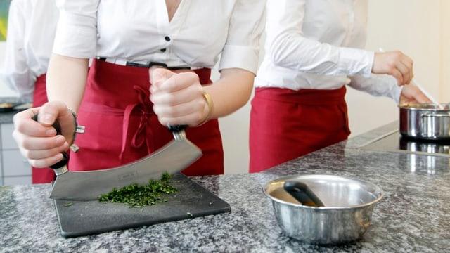 Zwei Frauen einer Hauswirtschaftsschule beim Kochen.