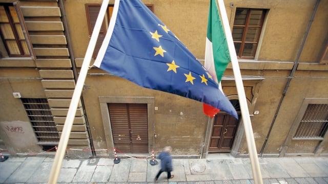 EU- und Italienflagge hängen an der Fassade, Blick auf eine Gasse.