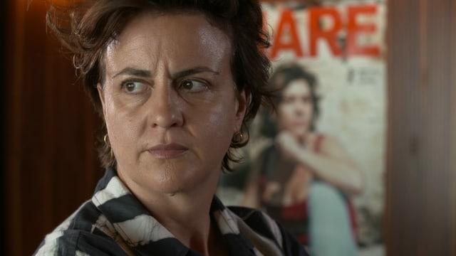 Eine Frau mit kurzen Haaren schaut zur Seite, im Hintergrund ein Filmplakat.