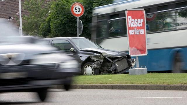 """Ein Unfallauto steht auf einem Mittelstreifen, daneben ein Plakat mit der Aufschrift """"Raser verlieren""""."""