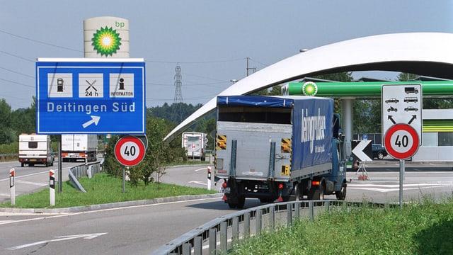Ein Lastwagen fährt auf eine Autobahnraststätte.