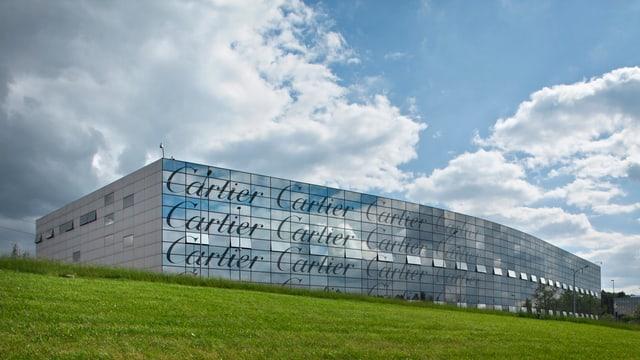Das Cartier-Werk in Villars: Eine gläserne Fabrikhalle auf einem grünen Feld.