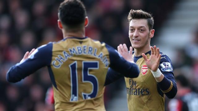Arsenals Mesut Özil klatscht bei Teamkollege Oxlade-Chamberlain ab.