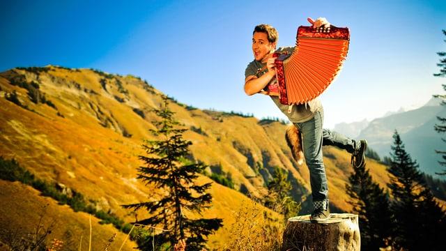 Marc A Trauffer mit Handorgel auf einem Baumstrunk in den Bergen.